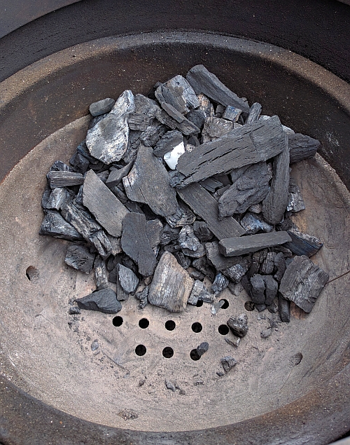 Charcoal is banked up on the right side of the Kamado Joe Classic firebox.  Just under the JoeTisserie spit rod.